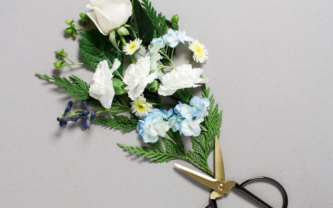 flatlay of a bouquet of flowers on a gray background with a scissors as the bouquet holder